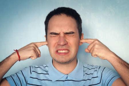 Lärm- und Hörkonzept - wütender junger Mann schreit, verstopft seine Ohren, um Probleme oder Stress abzulehnen, Kontrasteffekte. Kerl hielt sich mit den Fingern die Ohren zu