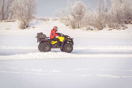 man driving a quad bike in the winter field. competition yellow ATV in the winter in the snow. The ATV rider in red uniform and helmet. Imagens