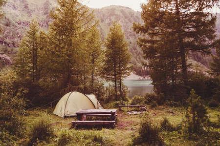 自然の中の森の中でその場しのぎの木製のテーブルの隣にテントキャンプ。