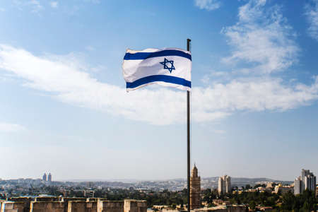 Israel flag flapping in the wind at good sunny day and old city background