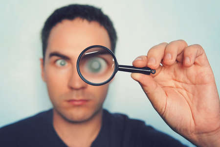 Male hand holding magnifying glass with blurred man's eye on foreground. Man glanses into the lens and his eye is magnified. Person uses loupe to magnify something. Examination with the help of lens