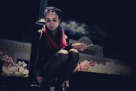 Giovane ragazza seduta sotto una lanterna per strada nella città notturna e fumando una sigaretta. Modello in posa come una prostituta. cattiva abitudine, abitudine dannosa, abitudine perniciosa, abitudine malsana Archivio Fotografico