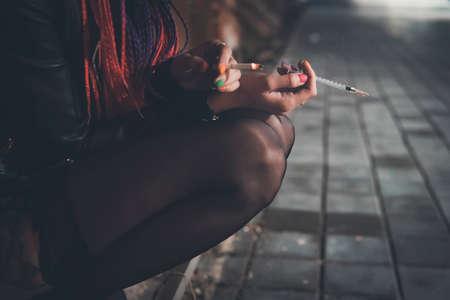 nel quartiere povero, tenendo in mano una sigaretta fumante con cannabis e una siringa con eroina. Problemi sociali del nostro tempo. il concetto di dipendenza e cattive abitudini Archivio Fotografico