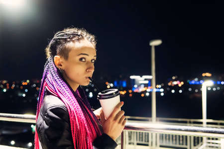 Smiling portrait of beautiful Caucasian girl in Italy enjoying coffee at night. a young woman drinks coffee through a straw from a disposable plastic Cup. cheerful, coffee to go. 版權商用圖片