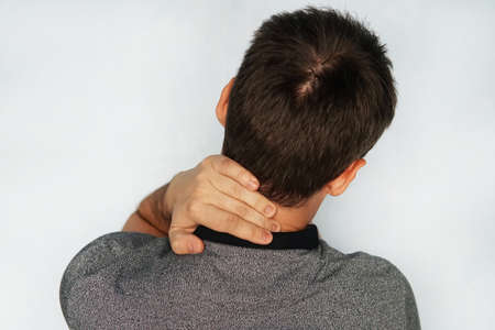 young man feeling exhausted and suffering from neck pain, Health concept. Neuralgia of the occipital nerve. meningitis, injuries, Myositis, weakness, tumors. Studio shot of sportsman with pain in neck