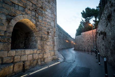 Ancient narrow street and typical stoned architecture in jewish quarter in Old City of Jerusalem, Israel. Old times walls and modern road pavement and lightings. Early morning in some ancient city.