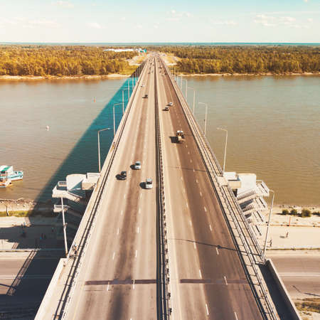 A view to the city bridge and river embankment. A straight line of a well-built highway across the river banks. City transportation across the river. Cars moving across a river bridge. Banks bridging