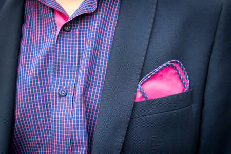 Vue sur la chemise et le manteau du jeune homme avec une poche un carré violet rougeâtre. Accessoires de costume pour hommes. Tenue de mariage des invités masculins. Style masculin. Tenue de dîner formelle pour hommes. Col homme déboutonné Banque d'images
