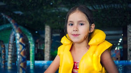 A close up of a cute smiling girl looking at camera at the water park background. A little smiley beautiful girl splashes water in indoor swimming pool. Water drops fall on the girl at aquapark pool.
