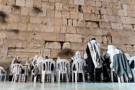 JERUSALEM ISRAEL - Octobe 24, 2018: Men in white tallits sitting on white chairs and praying to their religion at the Wailing Wall in old city of Jerusalem Editorial