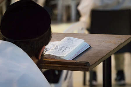 A religious man sitting and reading a torah at the Wailing Wall. Reading holy book of judaism at the western wall in Jerusalem old city. Head of the true believer in the background of the open book