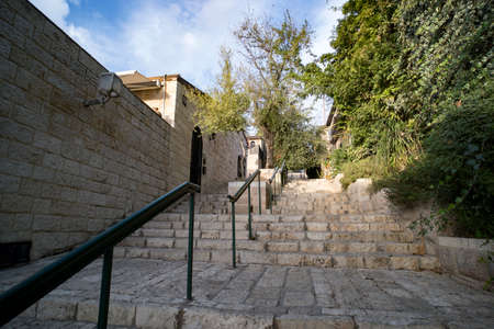 Down-top view of the vintage stone walls and stairs with modern handrails at a sunny summer day. Old city stairs surrounded by green trees and stone buildings. Town architecture of the past times
