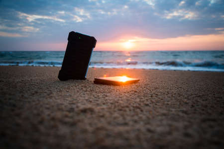 Powerbank in the sand on the background of the rising sun in the cloudy sky and blue sea. Alternative energy source. battery is charged by solar energy. Charging mobile devices in the wild. island.