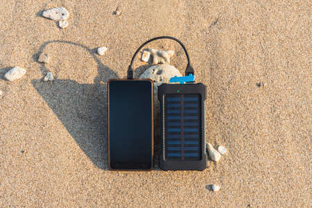 Portable solar panel is on the beach in the sand and charges the battery of the frameless mobile phone. use of solar energy in the wild on a desert island. water protection electronics waterproof Imagens