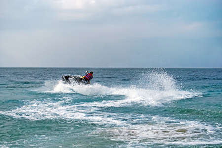 Young Man on Jet Ski, Tropical Ocean, Vacation Concept. water entertainment at sea. summer tourist vacation at the sea.