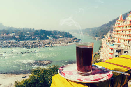 A glass of coffee on a plate against the background of the beautiful scenery of Rishikesh.. View of Ganga river embankment, Lakshman Jhula bridge and Tera Manzil Temple, Trimbakeshwar in Rishikesh