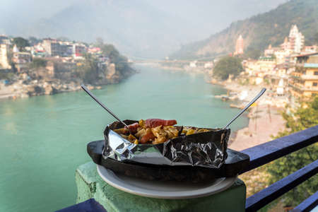 A dish of grilled and stewed vegetables on the background of the river Ganges. Rishikesh India., yoga city India, Gange River Ganga Ram Jhoola Jula