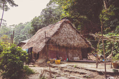 A little hut in in the tropical jungle. A rustic bamboo building with a thatched roof of a poor Indian family.