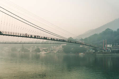 Ram Jhula is an iron suspension bridge situated in Rishikesh, Uttarakhand state of India. Evening dark landscape. Houses on the high slopes of the Himalayas