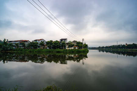 Hue, Vietnam. Pond in the city center city at background. Two-storey mansions on the lake. clouds reflected in water 免版税图像