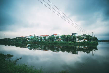 Hue, Vietnam. Pond in the city center city at background. Two-storey mansions on the lake. clouds reflected in water Reklamní fotografie