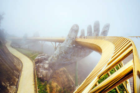 Danang , Vietnam. View in Fog of the Golden Bridge on Ba Na Hills in Da Nang on rainy day.