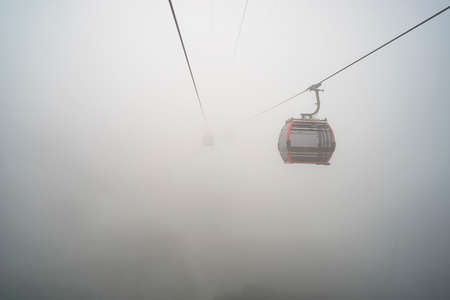Cable car in mountain a foggy day. the yellow funicular rises into the misty sky.