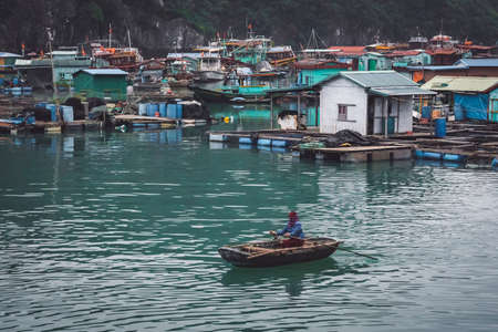 floating fish farm in ha long bay vietnam. Vietnamese woman on a fish farm. production of fish and shellfish in the sea. poor, indigent fisherwoman, fisher