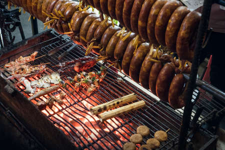 Smoked sausage hanging over the grill. The process of Smoking sausage. Cooking street food on grill 版權商用圖片
