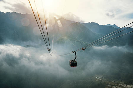 tourists travelling in transportation machine basket on fansipan mountain at sapa north of Vietnam. the sun sets behind mount Fansipan. Stock Photo
