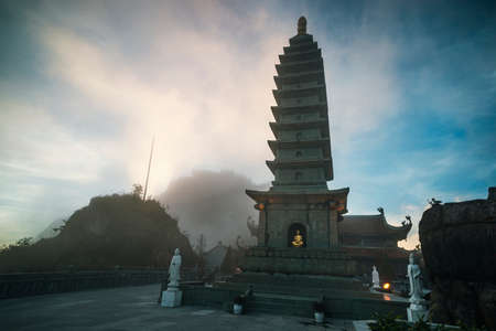 Stone Pagoda in Temple in the fog against the blue sky with dark clouds. on Fansipan mountain peak the highest mountain in Indochina.