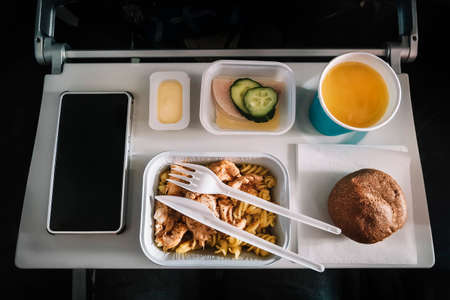 Inflight meal service tray for economy class, meat with pasta, seasoning fruit, salad, cucumber, a glass of juice and butter. selective focus.