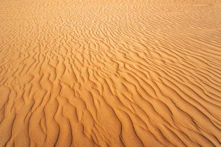Abstrakte Textur. Hintergrund mit glatten Sandlinien. Sanddünen Wellen im Sand. Streifen im Sand vom Wind Standard-Bild