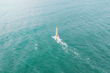 extreme man athlete swims on the wind surf on the sea wave against the blue sea and the horizon. Extreme water sports. movement of the red sail on the water. summer fun at sea.
