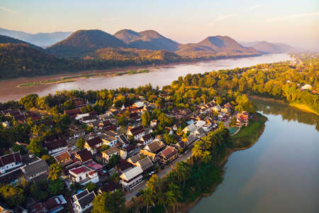 Aerial view of Luang Prabang and surrounding lush mountains of Laos. The Nam Kahn River, a tributary of the Mekong River, flows peacefully on the right.