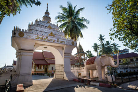 Entrance, with an open gate to a Buddhist temple. Vientiane, Laos.