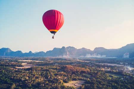 Globo aerostático rojo elevándose justo a tiempo para explorar la hermosa puesta de sol sobre Vang Vieng en Laos, sudeste asiático. Foto de archivo