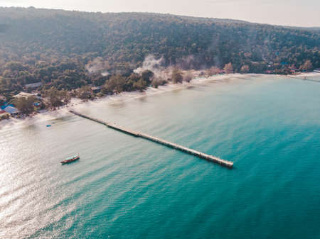 Birds eye drone aerial view of single pier in crystal clear blue sea on secluded beach on Cambodian island Koh Rong on sunny summer day