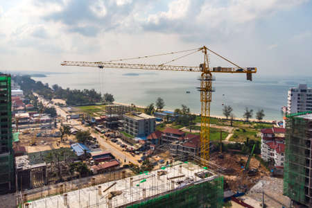 Construction of multi-storey buildings in Cambodia, Sihanoukville . Construction cranes on background of buildings. Storey building against the blue sky. Modern high-rise buildings under construction Stock Photo