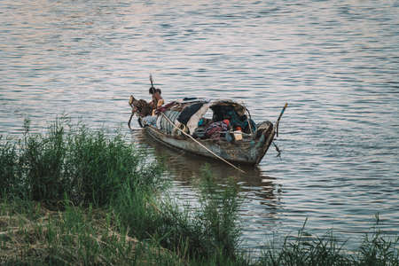 People in Boat on River Floating Village in Cambodia Asia. poor Cambodian family lives in a boat on the water. Poverty in Southeast Asia.