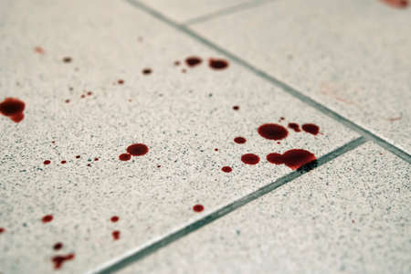 Conceptual image with blood on it resting on tiles on the floor Stock Photo