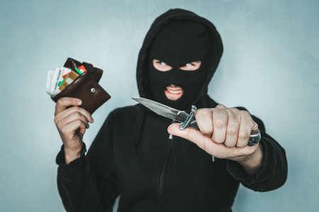 concept de vol criminel. Un voleur diabolique menace avec un couteau et tient un sac à main volé dans sa main. Danger de mort. Le voleur malveillant sourit. Banque d'images