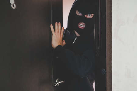 An evil gangster in a black mask covering his face broke the door and broke into the room and threatens the residents. concept of crime and violence. banditry, gangsterism, , racketeering, banditism,