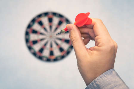 Business education success and target concept. Close up a hand is targeting the green dart arrow towards the center of dartboard. hit target. Success in business.