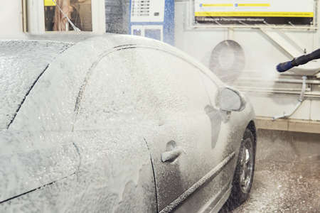 car is covered with foam to wash the car. Automatic car wash. Shampoo for cars. Cleaning process Фото со стока