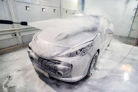 Auto ist mit Schaum bedeckt, um das Auto zu waschen. Automatische Autowäsche. Shampoo für Autos. Reinigungsprozess. Selbstbedienung, Standard-Bild