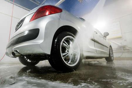 Selbstreinigendes stilvolles Auto in der Garage. Waschen kolesnogo Laufwerk. Auto mit Hochdruckwasser reinigen. Mann, der sein Auto unter Hochdruckwasser im Dienst wäscht