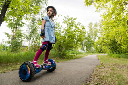 A little girl riding a electric self-balancing scooter. child is balancing on a gyroscooter. Personal eco transport, gyro scooter, smart balance wheel. Popular electric transport Imagens