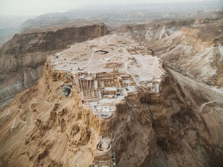 Aerial view of Masada fortress area, ancient fortification in the Southern District of Israel situated on top of an isolated rock plateau, akin to a mesa. Ruins on the eastern edge of Judaean Desert