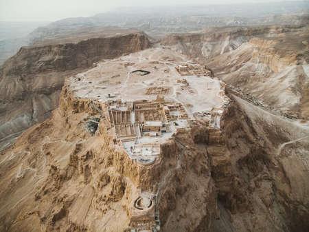 Luftaufnahme des Festungsbereichs Masada, einer alten Festung im südlichen Bezirk Israels, die auf einem isolierten Felsplateau liegt, ähnlich einer Mesa. Ruinen am östlichen Rand der Judäischen Wüste